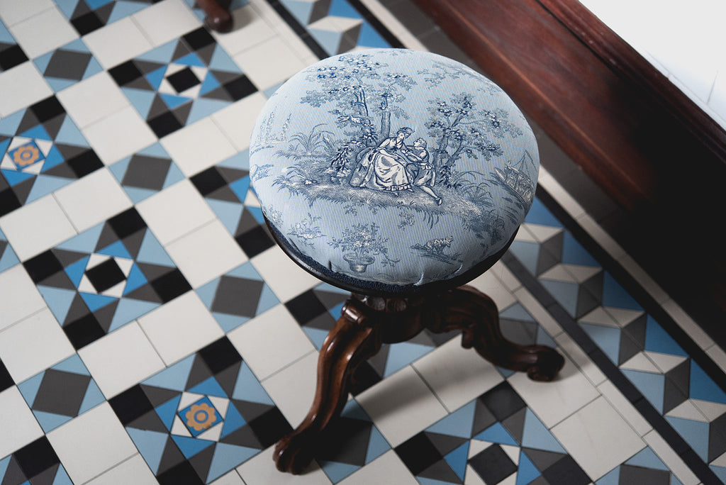 French Provincial stool sitting atop a tessellated tile floor