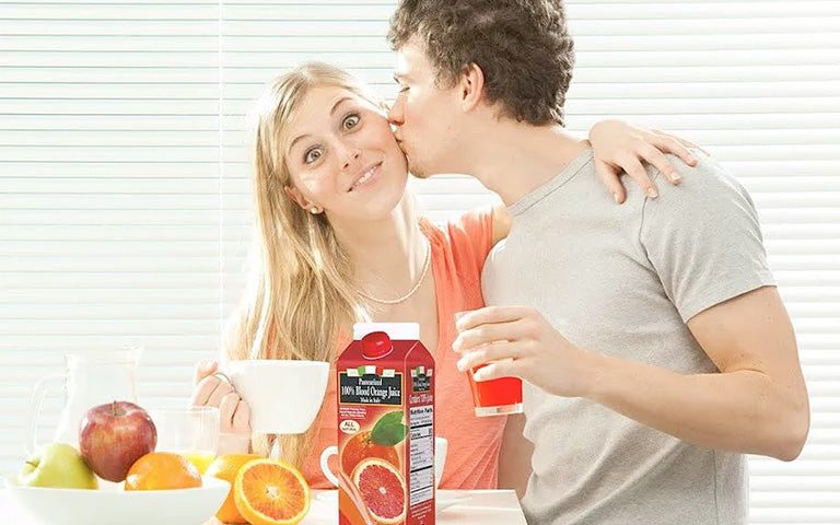 Man kissing Woman after trying Mongibello Blood Orange Juice