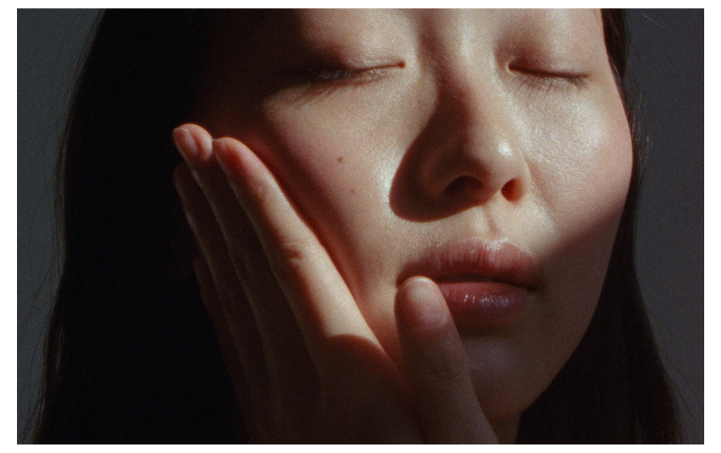 Close-up film still of a woman gently pressing Metadia Copia Face Oil into her cheek.