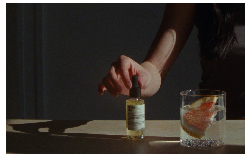 A women's shadowy hand is hovering over a bottle of Copia Face Oil, squeezing the pipette. Next to this is a glass of fizzy water with a fresh slice of grapefruit in it.
