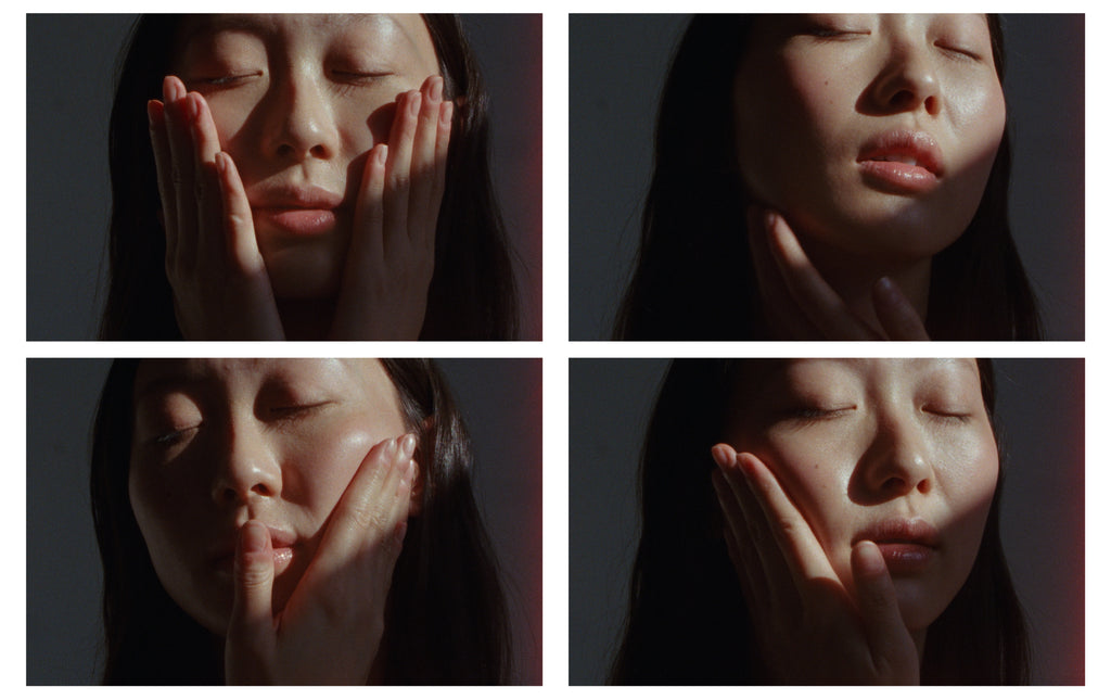 Four film stills in sequence showing a woman in a shaded room massaging her face gently with Metadia Copia Face Oil.