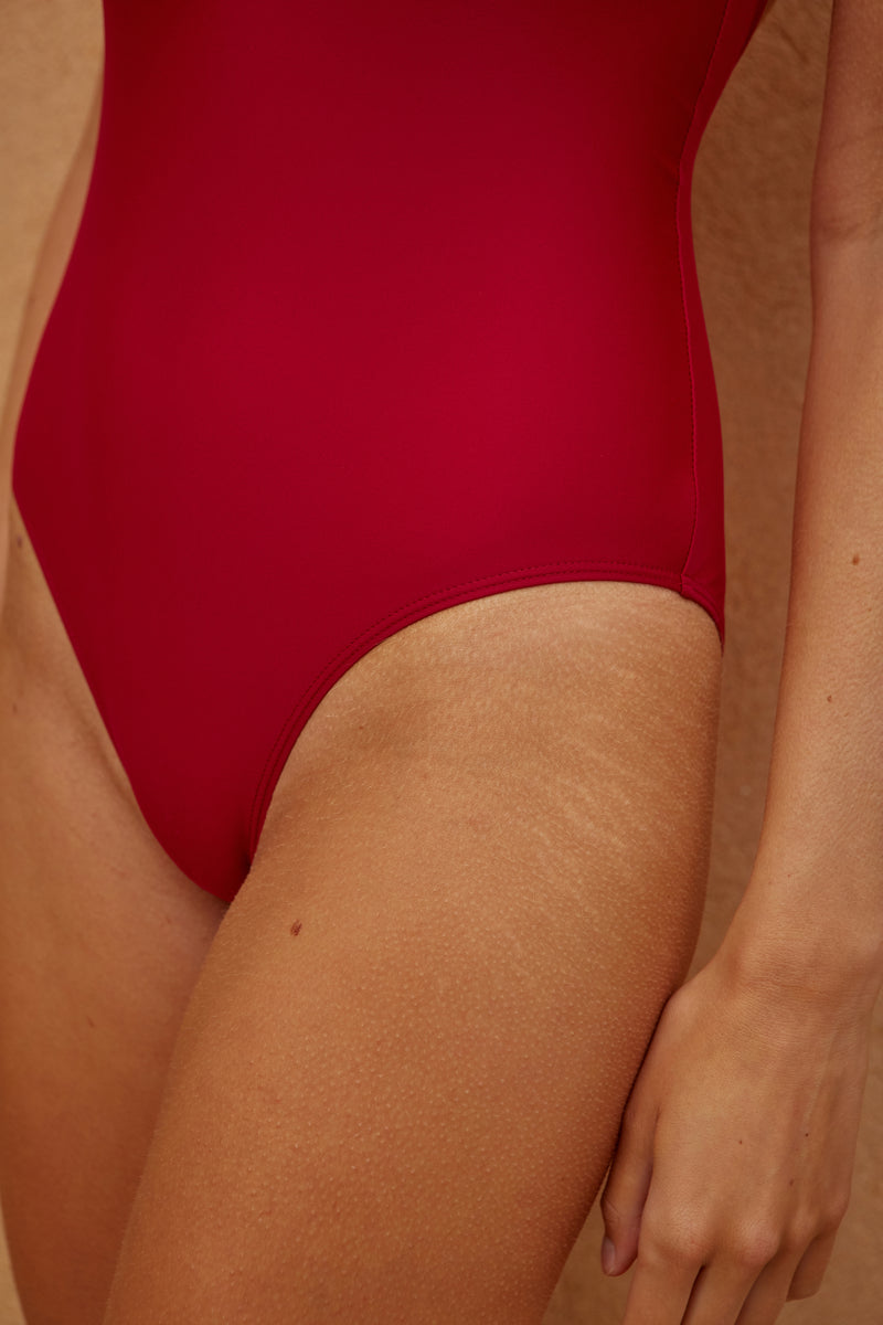 Initial S Maillot de bain femme 1 piècerouge décolleté triangle doré éco responsable fabrication française écologique nager bronzer plonger nylon recyclé swimwear swimsuit women revealing neckline red berry gold triangle sustainable made in france econyl recycled nylon sexy revealing neckline beachwear made from plastic waste natural beauty