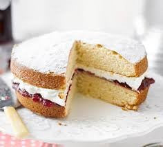 Victoria sponge cake with slice taken out of it.