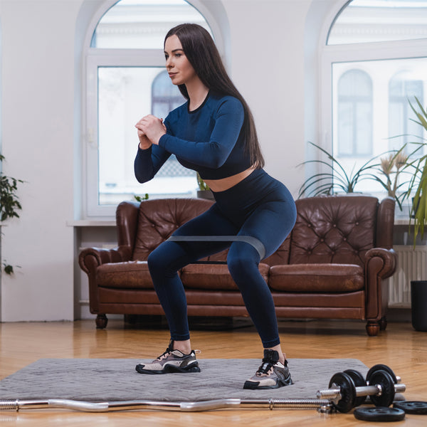 Woman exercising at home with resistance bands