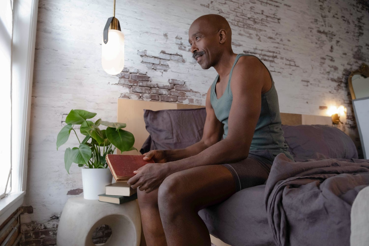 Ntare on bed with book