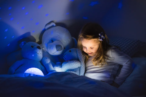 child reading in bed with night light