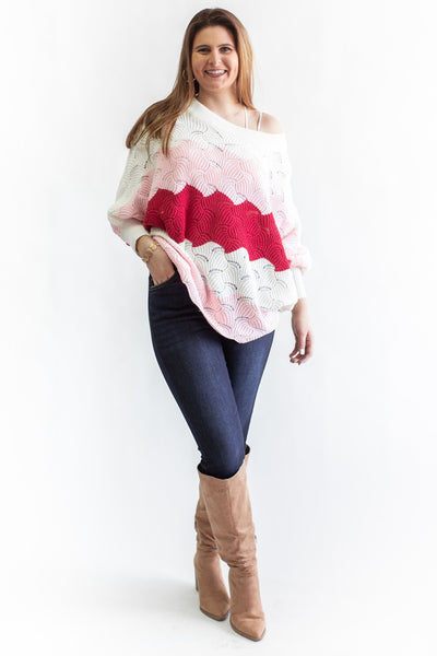 Model Wearing Color Block Knit Off Shoulder Sweater in White, Red, Pink with Jeans and Tall Taupe Boots Against White Background