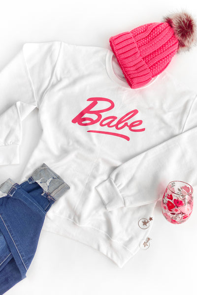 "White Sweatshirt with Barbie Inspired ""Babe"" Text On Front with Pink Beanie and Jeans"