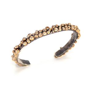 Nature inspired with organic styling on a simple oxidized silver cuff with a bronze seed-like nodules.