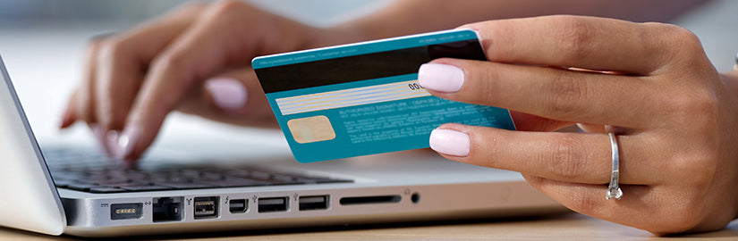 Woman with beautiful ring inputting credit card details into Philip Zetler Jewellers website