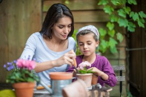 A mother and her daughter are repotting plants at the garden table