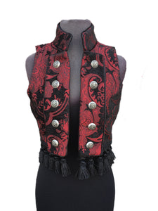 A beautiful gypsy/bellydancer/burlesque vest from the old country. A short vest with a stand-up collar in vintage european style, made in lush red/black tapestry fabric with black satin lining inside. Exquisite black satin piping trim all over. Front fastens back with ornate metal medieval lion buttons or can be undone and crossed over worn double-breasted fashion. Elaborate black tassel trim at the bottom. Great for any gothic, steampunk or bohemian affair.