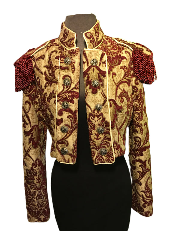 European cut, women's formal riding jacket. Beautiful short jacket with a stand-up collar made in rich tapestry fabric. Ten medieval lion buttons fasten front lapels which also can be unbuttoned and worn crossing over in double-breasted style. Matching smaller buttons fasten cuffs. Ornate bullion fringe epaulets add an authoritarian vibe. Lined in rich black satin. Wonderful!