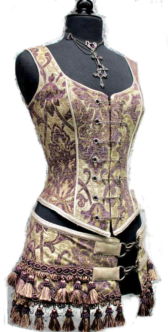 A Shrine classic!! A heavily constructed corset top in rich purple and ivory tapestry fabric with a great form fit. Heavy metal boning at sides and lycra stretch panel at back adds extra strong support. Fastens in front with seven large kilt pins but also zips in back for easy access. Rich ivory satin piping around armholes and neckline and ivory satin lining inside. Trimmed at the bottom with braided trim.