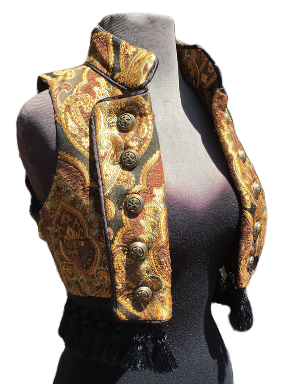 A beautiful pirate/bellydancer/burlesque vest from the old country. A short vest with a stand-up collar in vintage european style, made in rich gold/brown/green/black tapestry fabric with black satin lining inside. Exquisite black satin piping trim all over. Front fastens back with ornate metal medieval lion buttons or can be undone and crossed over worn double-breasted fashion. Elaborate black tassel trim at the bottom. Great for any bohemian affair. Splendid! Measurements: Small: Chest 32_ Ribcage 30_
