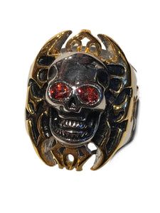 Skull ring with gold tinted cross background design and red gemstone eyes