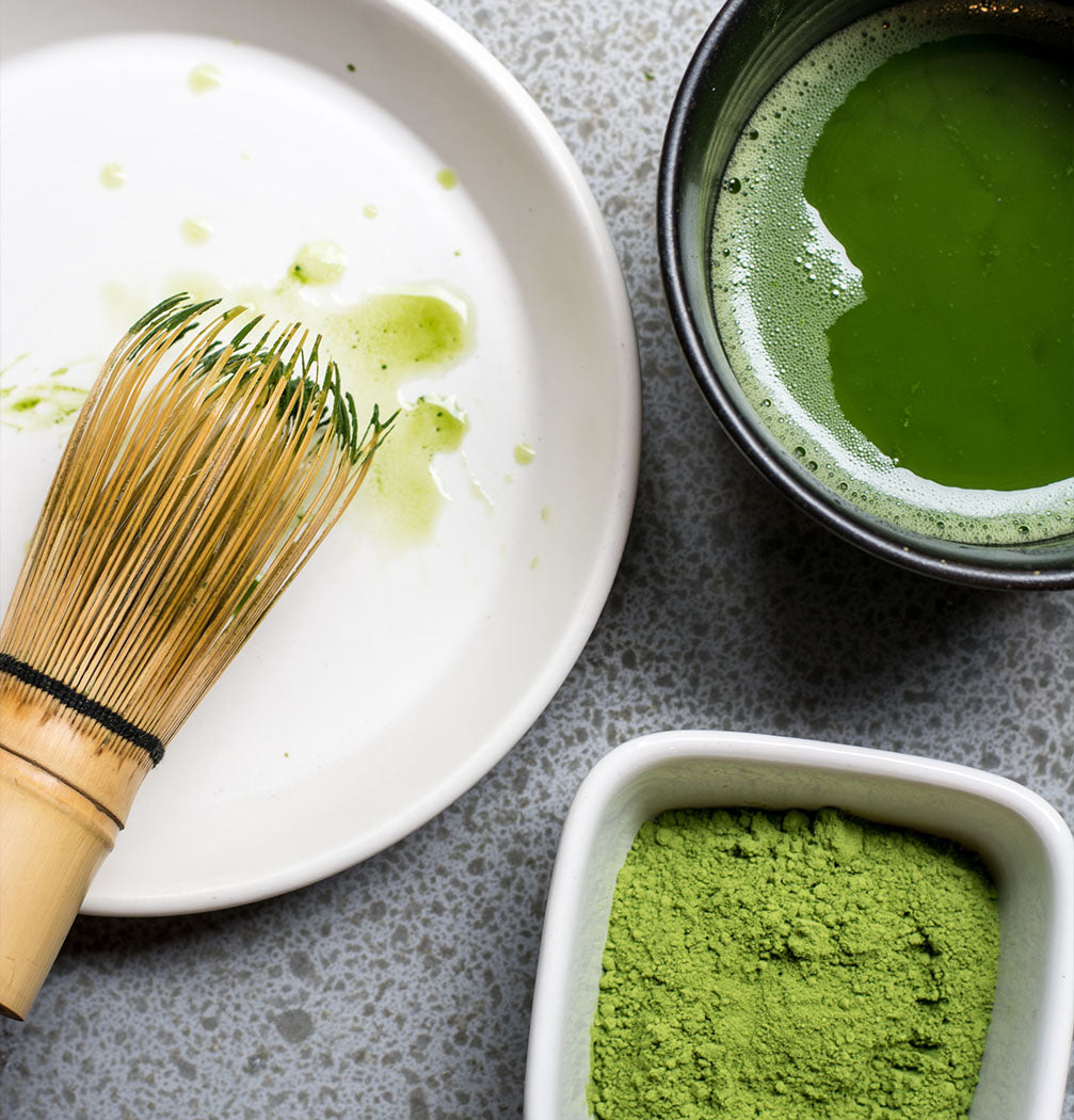 matcha powder and whisk on table