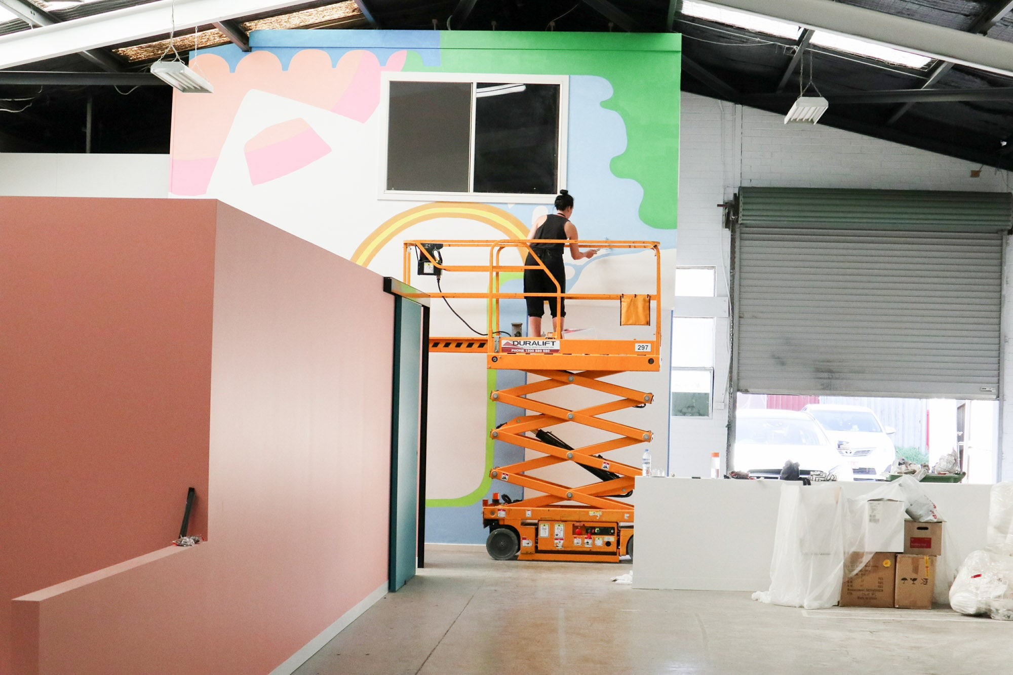Deb McNaughton Artist - working on Massive wall mural - painting on forklift - Zudis -  Melbourne