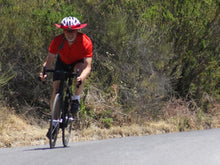 Load image into Gallery viewer, Riding a road bike with Da Brim Cycling Classic. Man on bike coming from downhill.