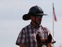 Load image into Gallery viewer, Male rider on horse with American flag in background. Rider is wearing the Da Brim Equestrian Petite Helmet Brim Visor in black.