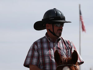 Male rider on horse with American flag in background. Rider is wearing the Da Brim Equestrian Petite Helmet Brim Visor in black.