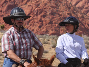Equestrian trail riders on horseback. Male wearing the Da Brim Equestrian Endurance Helmet Brim Visor in gray. Female is wearing the Da Brim Rezzo helmet visor in black.