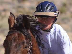 Close up photo of a woman riding her horse. She is wearing the Da Brim Rezzo helmet visor in tan.