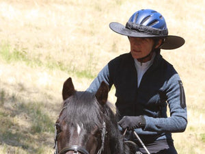 Horse and rider. Rider is wearing the Da Brim equestrian endurance helmet brim visor in black and is well shaded.
