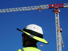 Load image into Gallery viewer, Construction worker Da Brim PRO Tech Lite Construction helmet visor brim in fluorescent yellow with reflective. Pictured with a crane.
