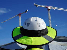 Load image into Gallery viewer, Da Brim PRO Tech Lite Construction helmet visor brim in fluorescent yellow with reflective on the job site. Rear view of brim pictured against background of a building and 2 cranes.