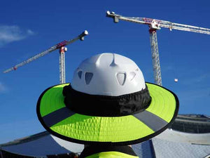 Da Brim PRO Tech Lite Construction helmet visor brim in fluorescent yellow with reflective on the job site. Rear view of brim pictured against background of a building and 2 cranes.