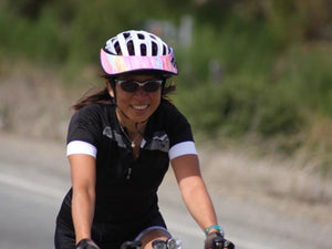 Female road biker riding with a Da Brim Rezzo helmet visor in pastel ribbons.