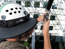 Load image into Gallery viewer, Da Brim PRO Tech Construction Helmet Visor Brim in gray at work. Man performing rigging duties at height while working and wearing the Da Brim PRO Tech Construction Helmet Visor Brim in gray.