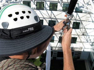 Da Brim PRO Tech Construction Helmet Visor Brim in gray at work. Man performing rigging duties at height while working and wearing the Da Brim PRO Tech Construction Helmet Visor Brim in gray.