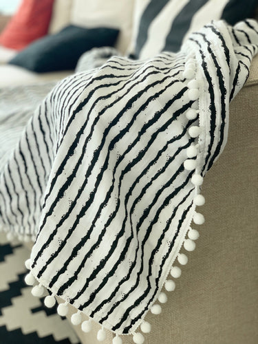 cotton blanket with pom-poms in black white stripes design