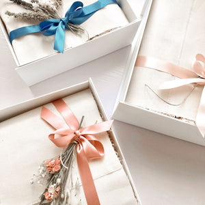 Amala Curation's White Gift Boxes, Set of 3 on a white surface, wrapped with cotton fabric, pink and blue ribbons, and dried flowers.