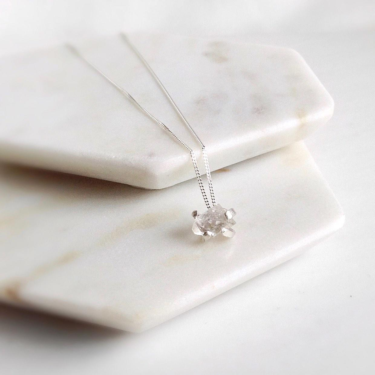 Wearth Diamond Necklace laid on 2 white and grey marble coasters