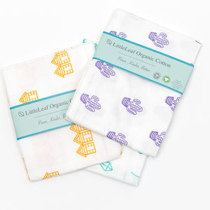 Little Leaf Organic Cotton Muslin Cloths - 3 colours laid flat on white surface (white with orange beach huts, white with purple cacti, white with blue kites)