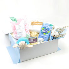 Load image into Gallery viewer, Amala Curations Luxury Ethical Gift Box/ Hamper; white box lined with blue fabric, with 6 organic gifts (cotton crochet turtle, organic lactation tea, organic baby bottom balm, organic nipple balm odylique, organic cornish sea salt chocolate bar, organic cotton cream babygrow, and a mini flower bouquet - baby boy gift box