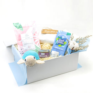 Amala Curations Luxury Ethical Gift Box/ Hamper; white box lined with blue fabric, with 6 organic gifts (cotton crochet turtle, organic lactation tea, organic baby bottom balm, organic nipple balm odylique, organic cornish sea salt chocolate bar, organic cotton cream babygrow, and a mini flower bouquet - baby boy gift box
