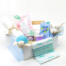 Load image into Gallery viewer, Amala Curations Luxury Ethical Gift Box/ Hamper; white box lined with cream fabric, with 9 organic gifts (cotton blanket, blue cotton crochet turtle, organic lactation tea, organic coconut oil kokoso, organic baby bottom balm, organic nipple balm odylique, organic muslin cloth with blue kites on, organic cornish sea salt chocolate bar, organic cotton cream babygrow, and a mini flower bouquet - baby boy gift box