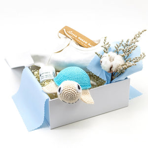 White Luxury Gift Box lined with blue cotton fabric, with Cream Babygrow, Odylique Nipple Balm, Blue Crochet Organic Cotton Turtle, and a flower bouquet with dried cotton