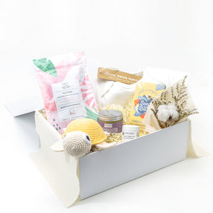 Amala Curations Luxury Ethical Gift Box/ Hamper; white box lined with cream fabric, with 6 organic gifts (cotton crochet turtle, organic lactation tea, organic baby bottom balm, organic nipple balm odylique, organic lemon chocolate bar, organic cotton cream babygrow, and a mini flower bouquet - gender neutral gift box