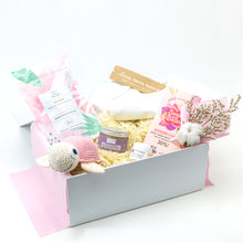Load image into Gallery viewer, Amala Curations Luxury Ethical Gift Box/ Hamper; white box lined with pink fabric, with 6 organic gifts (cotton crochet turtle, organic lactation tea, organic baby bottom balm, organic nipple balm odylique, organic raspberry & vanilla chocolate bar, organic cotton cream babygrow, and a mini flower bouquet - baby girl gift box