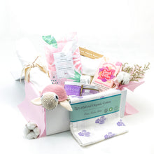Load image into Gallery viewer, Amala Curations Luxury Ethical Gift Box/ Hamper; white box lined with pink fabric, with 9 organic gifts (cotton blanket, pink cotton crochet turtle, organic lactation tea, organic coconut oil kokoso, organic baby bottom balm, organic nipple balm odylique, organic muslin cloth with purple cacti on, organic raspberry & vanilla chocolate bar, organic cotton cream babygrow, and a mini flower bouquet -baby girl pink gift box