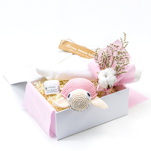 White Luxury Gift Box lined with pink cotton fabric, with Cream Babygrow, Odylique Nipple Balm, Pink Crochet Organic Cotton Turtle, and a flower bouquet with dried cotton