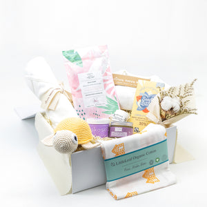 Amala Curations Luxury Ethical Gift Box/ Hamper; white box lined with cream fabric, with 9 organic gifts (cotton blanket, cotton crochet turtle, organic lactation tea, organic coconut oil kokoso, organic baby bottom balm, organic nipple balm odylique, organic muslin cloth with orange beach huts on, organic lemon chocolate bar, organic cotton cream babygrow, and a mini flower bouquet - gender neutral gift box