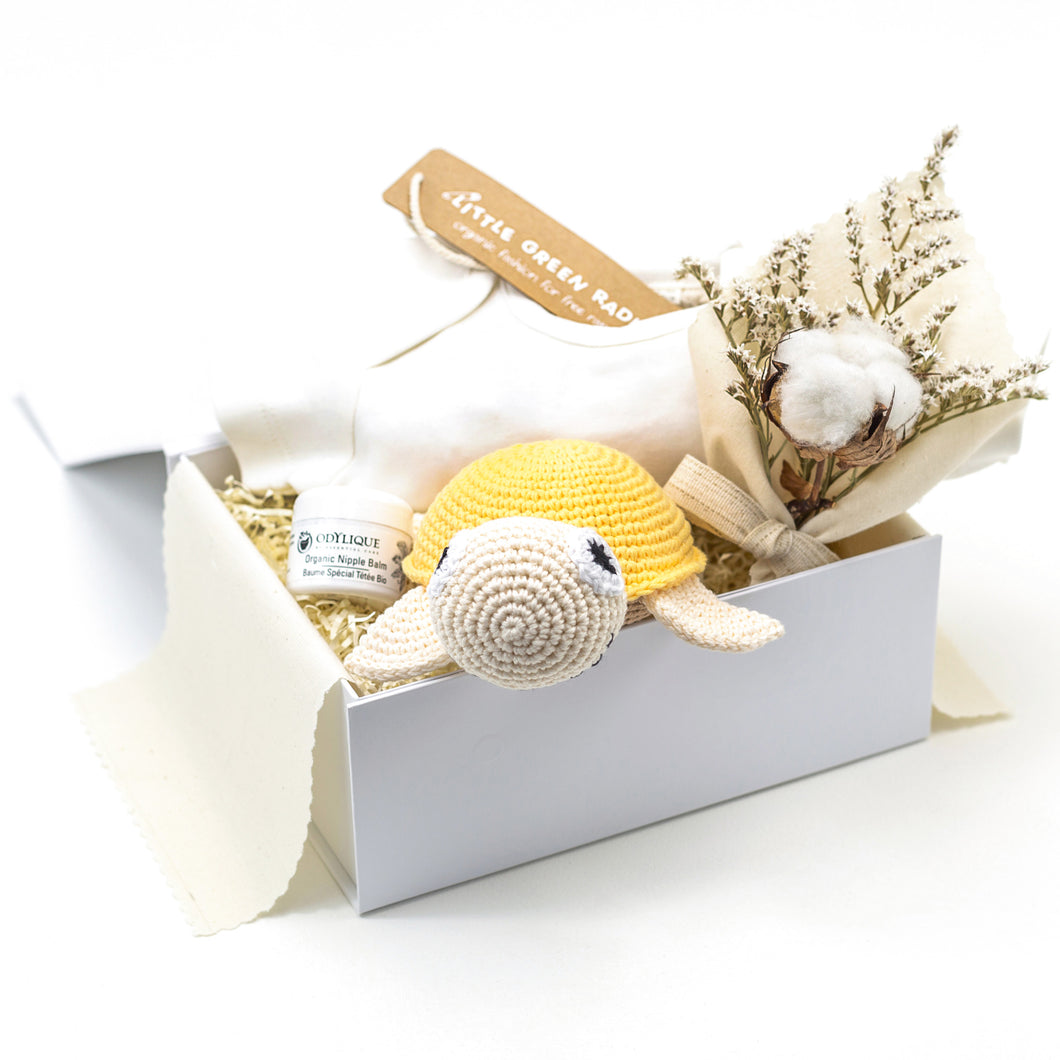 White Luxury Gift Box lined with cream cotton fabric, with Cream Babygrow, Odylique Nipple Balm, Yellow Crochet Organic Cotton Turtle, and a flower bouquet with dried cotton