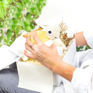 White Luxury Gift Box lined with cream cotton fabric, with Cream Babygrow, Odylique Nipple Balm, Yellow Crochet Organic Cotton Turtle, and a flower bouquet with dried cotton - opened on a lady's lap with her holding the turtle. the lady is wearing a white shirt and blue jeans.