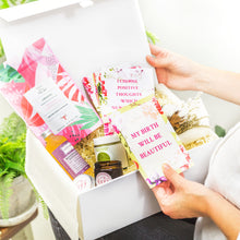 Load image into Gallery viewer, Lady's hands holding Amala Curations White Luxury Gift Box, lined with cream fabric, with 5 organic products (relaxing bath and body oil, stretch butter, affirmation cards, mama candle, raspberry leaf tea) and a cotton flower bouquet